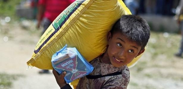 Sobrevivente do terremoto carrega um saco de arroz durante uma distribuição de alimentos