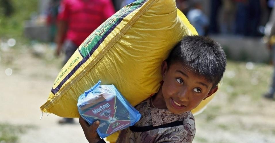"""16.mai.2015 - Sobrevivente do terremoto carrega um saco de arroz durante uma distribuição de alimentos no Jaharsingh Pauwa, no Nepal. Dois fortes terremotos atingiram o país em menos de um mês, deixando mortos e feridos. As crianças afetadas estão """"enfrentando uma carga emocional sem precedentes"""", advertiu a ONU"""