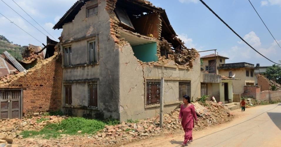 17.mai.2015 - Nepalesa caminha perto de casas danificadas por terremotos, nos arredores de Katmandu. Os sismos deixam mortos, feridos e milhares de desabrigados