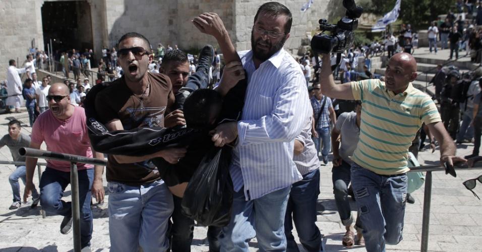 17.mai.2015 - Palestinos carregam homem que foi ferido durante confronto com a polícia de Israel do lado de fora do Portão de Damasco, na Antiga Jerusalém. Nacionalistas israelenses participam da ''Marcha da Bandeira'', que marca o 48° aniversário da vitória sobre os árabes na Guerra dos Seis Dias em 1967