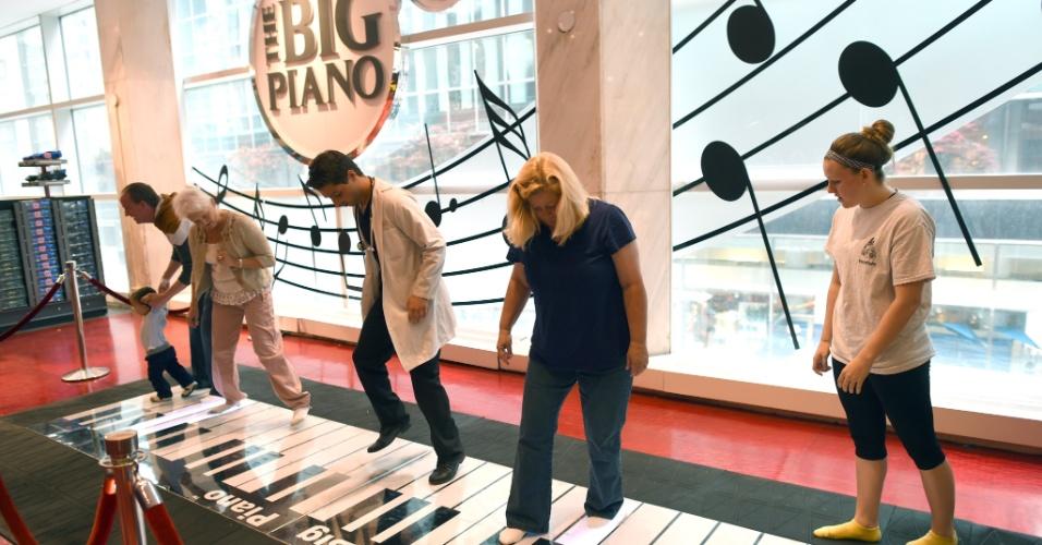 18.mai.2015 - Consumidores dançam no Big Piano da loja FAO Schwarz, na Quinta Avenida, em Nova York (EUA), nesta segunda-feira (18). A famosa loja de brinquedos, fundada em 1982, é a mais antiga do ramo nos Estados Unidos. Ela funciona no local desde 1986, mas será fechada em julho deste ano devido ao aumento nos aluguéis e se mudará para um novo endereço. O brinquedo ficou famoso no filme