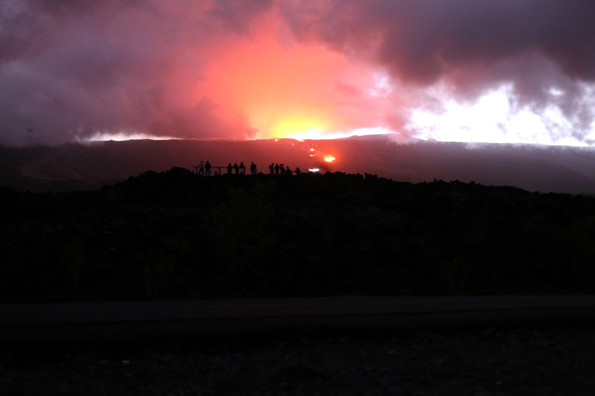 18.mai.2015 - Espectadores assistem à erupção do vulcão Piton de la Fournaise nesta segunda-feira (18), na ilha francesa de La Reunion, no oceano Índico. O vulcão começou a expelir cinzas e lavas no domingo (17)