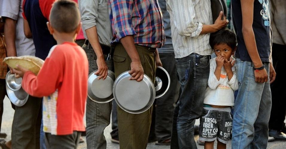 19.mai.2015 - Nepaleses fazem fila para receber alimentos e itens básicos em um acampamento para sobreviventes do terremoto no Nepal, em Katmandu. Cerca de 8.500 pessoas foram mortas no desastre que destruiu mais de meio milhão de casas e deixou um grande número de nepaleses sem abrigo, apenas algumas semanas antes das chuvas do período de monção