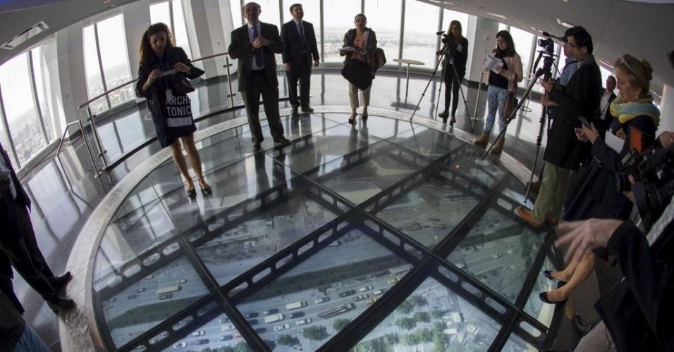 20.mai.2015 - Jornalistas e fotógrafos participam de coletiva no SkyPortal, um disco de quatro metros de largura, que transmite imagens em alta definição ao vivo do que acontece na rua, em deck de observação do One World Observatory, que fica no 100º andar da torre One World Trade Center, em Nova York (EUA). O One World Observatory será aberto ao público em 29 de maio