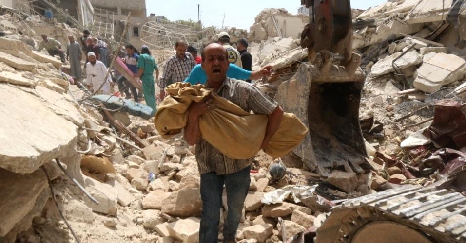 20.mai.2015 - Sírio carrega um corpo removido dos escombros de edifícios após um ataque com bomba feito pelo governo do ditador Bashar al-Assad, no bairroo de Qadi Askar, na cidade de Aleppo, nesta quarta-feira (20)