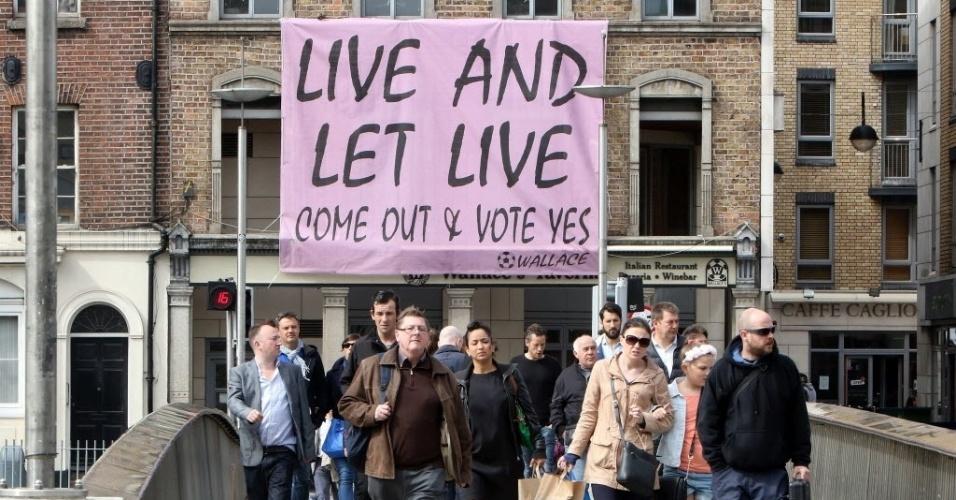 21.mai.2015 - Pedestres passam por uma bandeira em favor do casamento entre pessoas do mesmo sexo com os dizeres