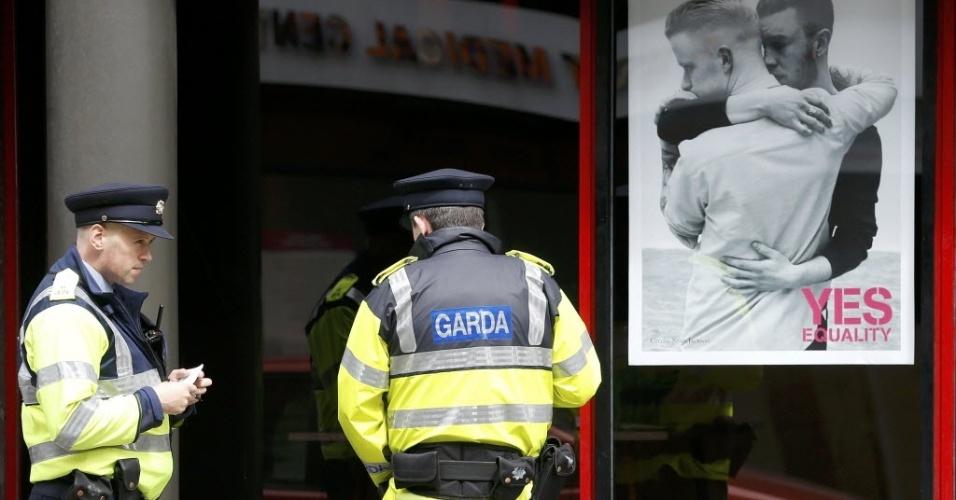 22.mai.2015 - Agentes da polícia param para falar com um morador de rua que dorme no local (não aparece na foto) ao lado de um cartaz em favor do casamento entre pessoas do mesmo sexo. Nesta sexta-feira (22), o país realiza um referendo para decidir sobre a legalidade da união gay. O
