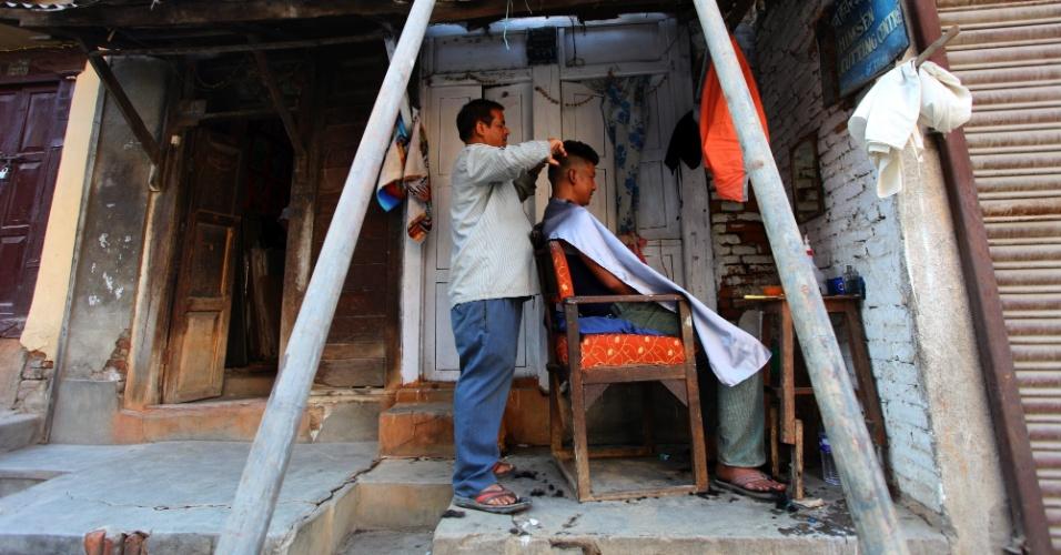 22.mai.2015 - Barbeiro corta o cabelo de cliente do lado de fora de uma casa em Katmandu, Nepal, danificada pelos terremotos que atingiram o país