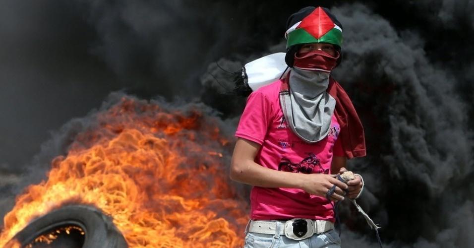 22.mai.2015 - Manifestante palestino se prepara para lançar pedra em direção às forças de segurança israelenses durante confrontos após uma manifestação contra a desapropriação de terras palestinas por Israel na aldeia de Kafr Qaddum, perto de Nablus, na Cisjordânia