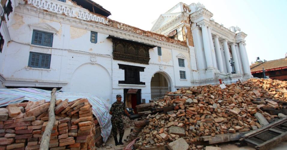 22.mai.2015 - Membro do Exército monta guarda na entrada do Palácio Gaddi Baithak, na praça Durbar Hanumandhoka, em Katmandu, no Nepal. A obra foi parcialmente destruída depois que terremotos atingiram o país