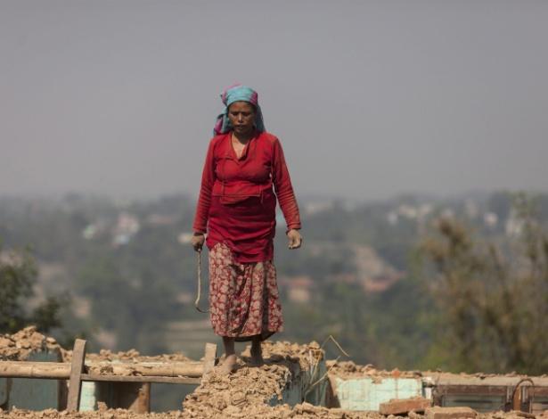 22.mai.2015 - Mulher tenta recuperar pertences dos escombros de sua casa em Changunarayan, próximo de Bhaktapur, no Nepal, destruída pelo terremoto que atingiu o país em 25 de abril, e deixou mais de 8.000 mortos
