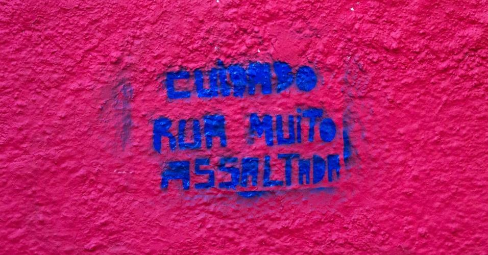 22.mai.2015 - Pintura em muro alerta sobre risco de assaltos em viela entre as ruas Iquiririm e Professor Vicente Peixoto, no bairro do Jardim Rizzo, subdistrito do Butantã, na zona oeste de São Paulo (SP). Moradores resolveram grafitar avisos de precaução após o local ter sido alvo de assaltos e sequestros
