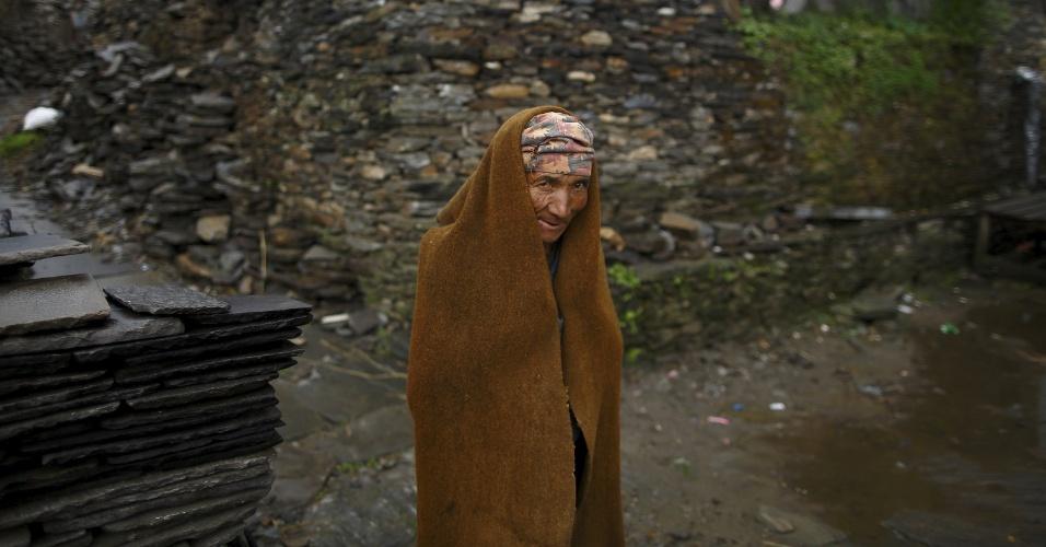 22.mai.2015 - Tes Bahadur Ghale, 60, uma das vítimas do terremoto que atingiu o Nepal em 25 de abril, se cobre com um manto de lã de ovelha enquanto caminha em direção a sua casa que desabou no distrito de Gorkha