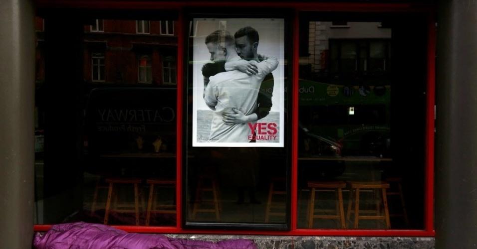 22.mai.2015 - Um morador de rua dorme abaixo de um cartaz em favor do casamento entre pessoas do mesmo sexo. Nesta sexta-feira (22), o país realiza um referendo para decidir sobre a legalidade da união gay. O