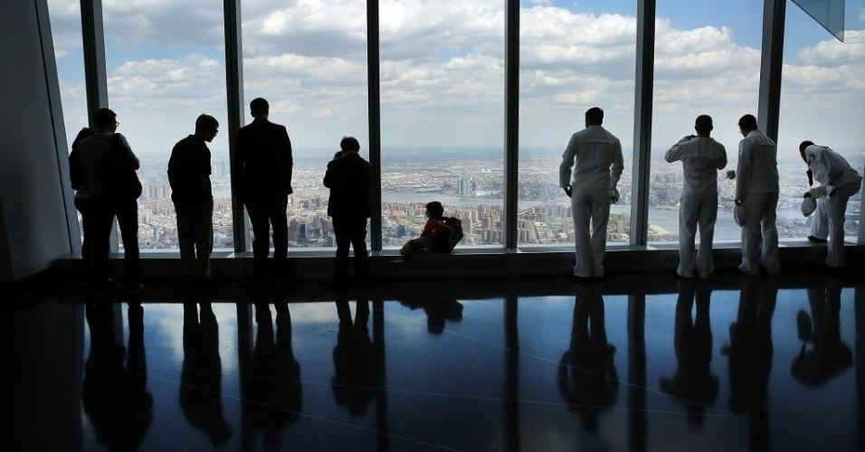 22.mai.2015 - Visitantes observam a cidade de Nova York, nos Estados Unidos, do mirante do One World Trade Center, nesta sexta-feira (22). A plataforma de observação fica no topo do arranha-céu de 104 andares no antigo local das Torres Gêmeas, que será aberta ao público no dia 29 de maio
