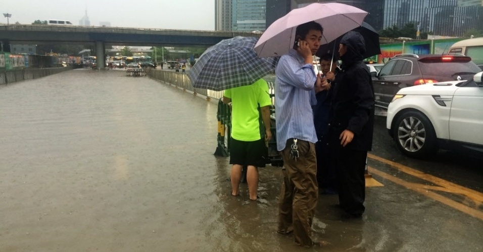 23.mai.2015 - Funcionários da prefeitura de Shenzhen, na província de Guangdong, no sul da China, caminham em uma área alagada da cidade neste sábado (23). As tempestades dos últimos dias provocaram pelo menos 35 mortes e deixaram 13 desaparecidos na região