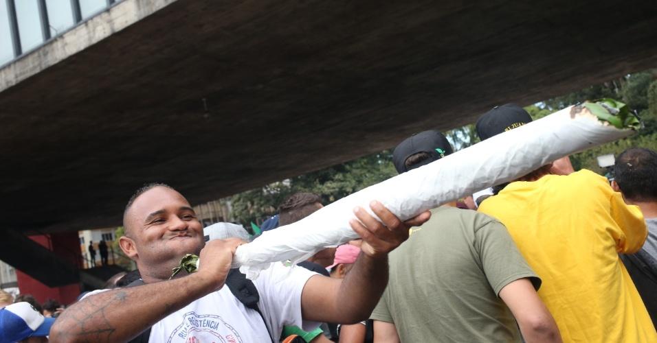23.mai.2015 - Manifestante simula fumar um cigarro gigante de maconha durante marcha na capital paulista que pede a legalização da uso e produção da droga