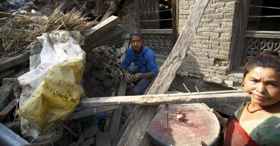 25.mai.2015 - Mãe e filho recuperam cebolas de casa em ruínas um mês após o primeiro terremoto atingir o Nepal, em Katmandu