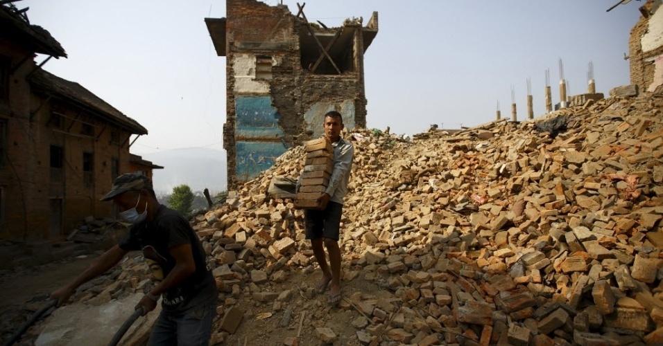 25.mai.2015 - Morador carrega tijolos de casas destruídas um mês após o primeiro terremoto atingir o Nepal, em Katmandu