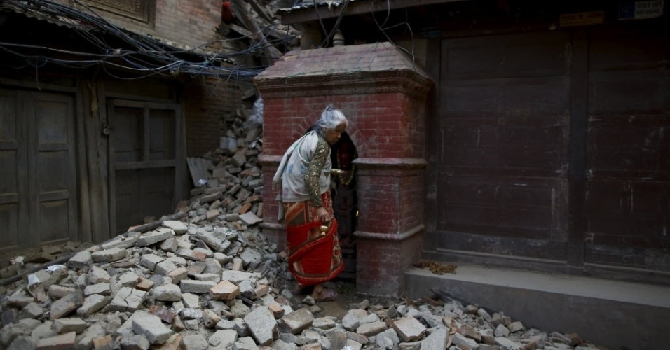 25.mai.2015 - Moradora retornar para casa em ruínas após orações, em Katmandu, um mês depois do devastador terremoto que destruiu parte do país