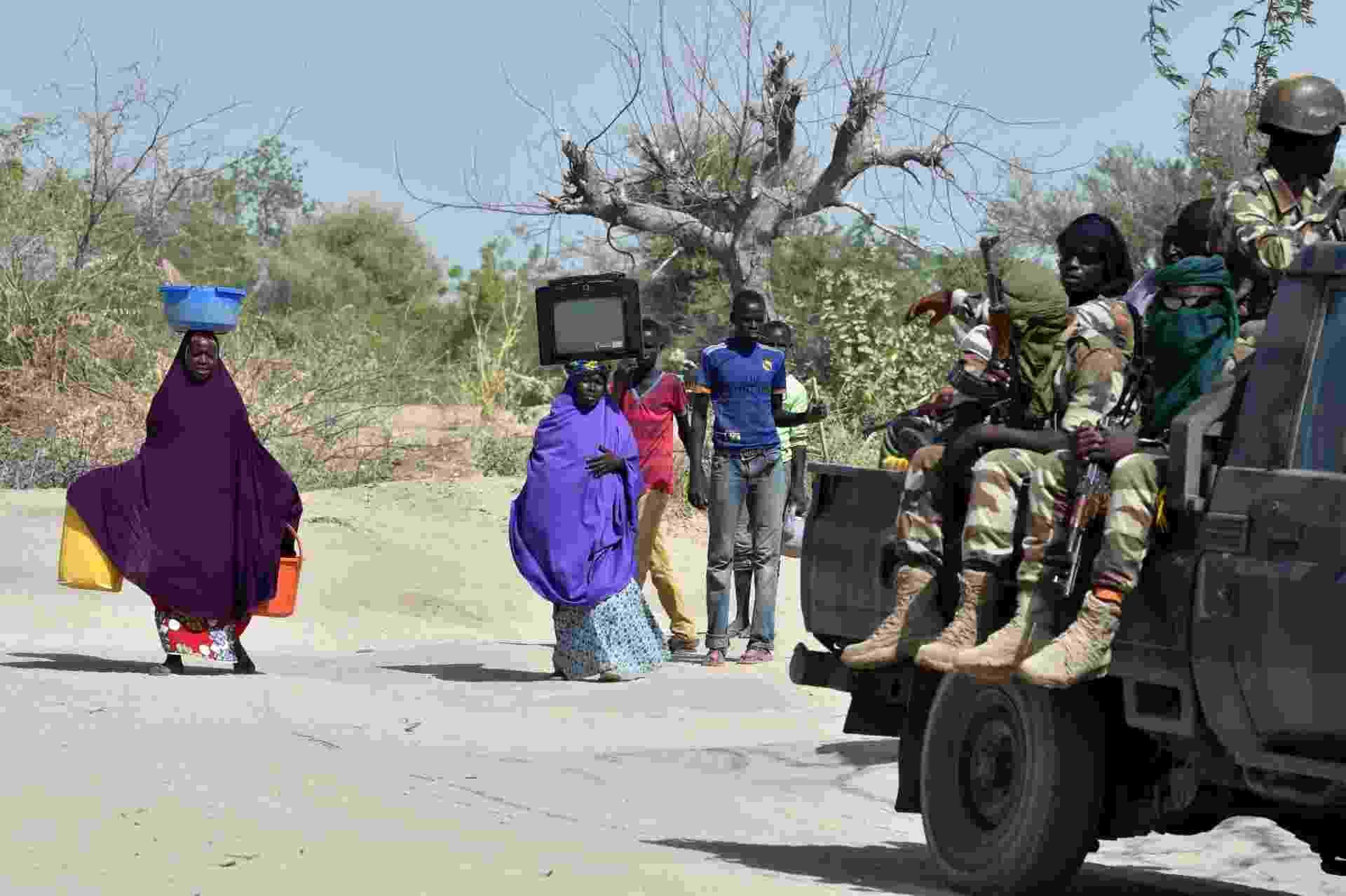25.mai.2015 - Nigerianos da cidade de Malam Fatori e de povoados vizinhos, próximos à fronteira entre Níger e Chade, estão abandonando suas casas devido aos ataques do grupo Boko Haram. Os habitantes estão buscando refúgio em Bosso, cidade que conta com a presença de tropas de Níger e Chade. O grupo Boko Haram, que pretende criar um estado islâmico no nordeste da Nigéria, perdeu alguns territórios e cidades que haviam sido capturadas desde que uma ofensiva lançada em fevereiro pelas forças armadas da Nigéria, com apoio do Níger, Chade e Camarões, forçou os radicais islamitas a abandonar essas áreas - Issouf Sanogo/AFP