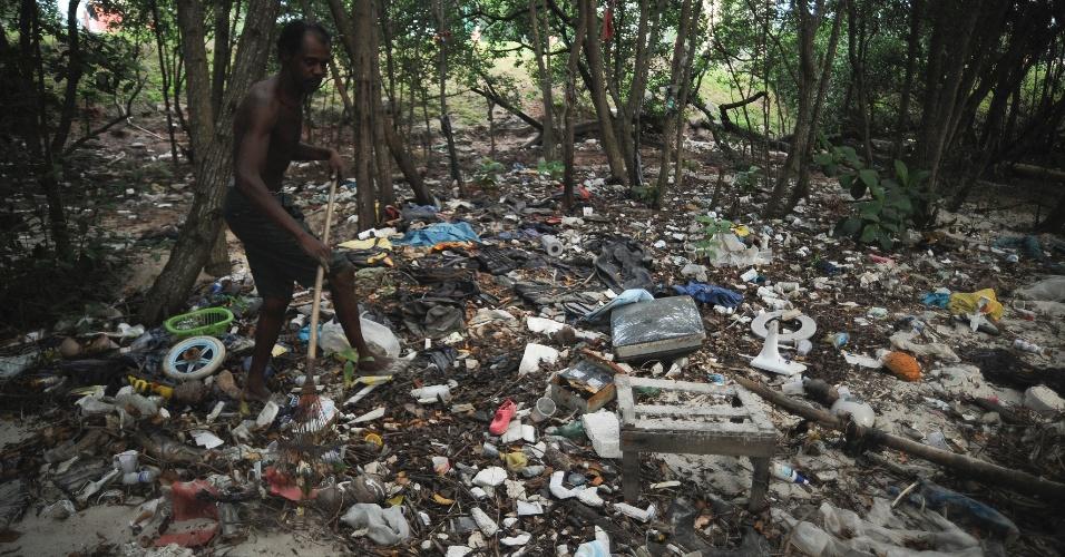 29.mai.2015 - O catador Arnaldo Nascimento, 39, que construiu uma pequena casa de palafita em uma colônia de pescadores próxima ao Complexo da Maré, na zona norte do Rio de Janeiro, às margens da baía de Guanabara, se esforça para manter o local limpo. Todos os dias, diz, a praia se enche de lixo