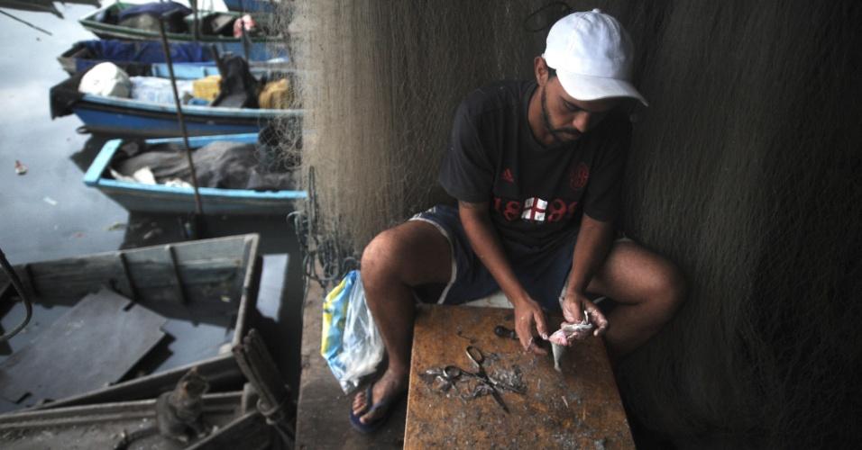 29.mai.2015 - Um pescador limpa peixe em uma colônia localizada embaixo do viaduto da Linha Vermelha, entre as favelas Pinheiros e Salsa e Merengue. Os pescadores que têm como base os arredores do Complexo da Maré, na zona norte do Rio de Janeiro, reclamam da poluição e do assoreamento da baía da Guanabara
