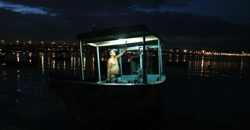 29.mai.2015 - Pescador sai para pescar à noite, com a maré cheia. Os pescadores que têm como base os arredores do Complexo da Maré, na zona norte do Rio de Janeiro, reclamam da poluição e do assoreamento da baía da Guanabara