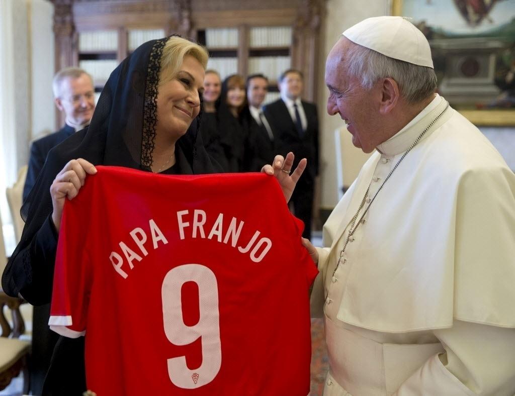 28.mai.2015 - Papa Francisco é presenteado pela presidente da Croácia, Kolinda Grabar-Kitarovic, com uma camisa da seleção de futebol o país que tem seu nome escrito em croata. O encontro foi realizado nesta quinta-feira (28) no Vaticano