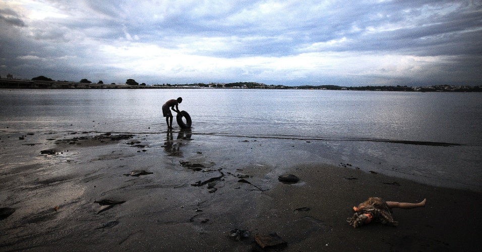 29.mai.2015 - O catador Arnaldo Nascimento, 39, recolhe um pneu. Ele construiu uma pequena casa de palafita em uma colônia de pescadores próxima ao Complexo da Maré, na zona norte do Rio de Janeiro, às margens da baía de Guanabara, e se esforça para manter o local limpo. Todos os dias, diz, a praia se enche de lixo