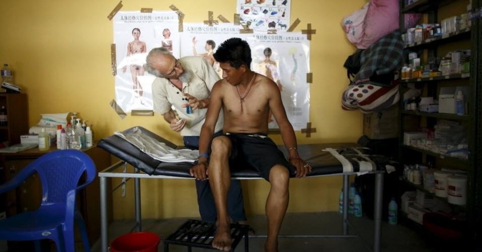 29.mai.2015 - O médico francês Richard Patrick faz tratamento de acupuntura em vítima dos terremotos, em campo médico temporário em um monastério tibetano, em Kathmandu, no Nepal. De acordo com um funcionário, 492 vítimas do bairro de Langtang foram abrigadas temporariamente no mosteiro depois de serem resgatadas de suas aldeias