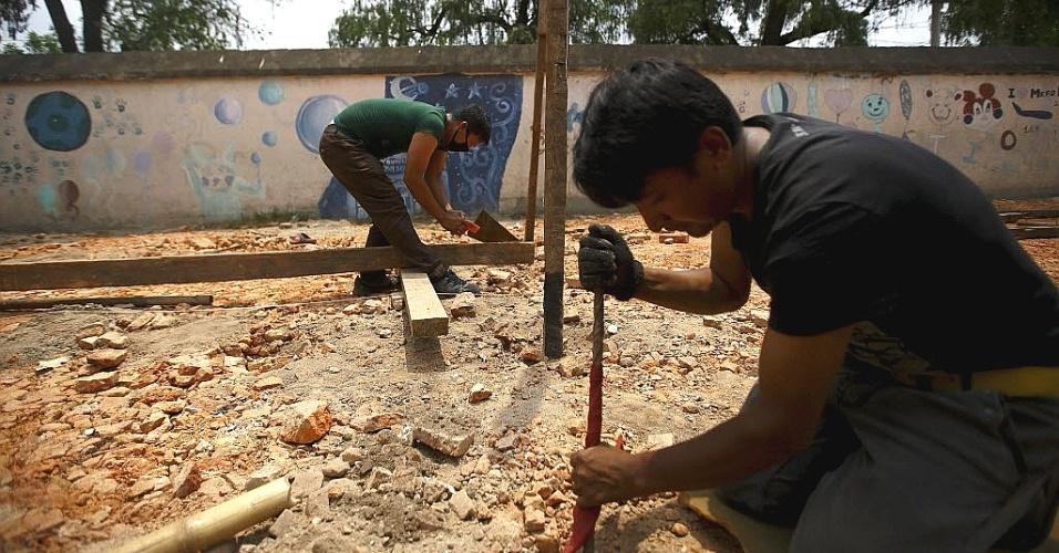 29.mai.2015 - Operários trabalham na construção de sala de aula temporária no terreno onde havia uma escola, em Katmandu, no Nepal. De acordo com a mídia local, o Ministério da Educação tem declarado que as escolas serão reabertas em 31 de maio em 14 distritos afetados pelos terremotos