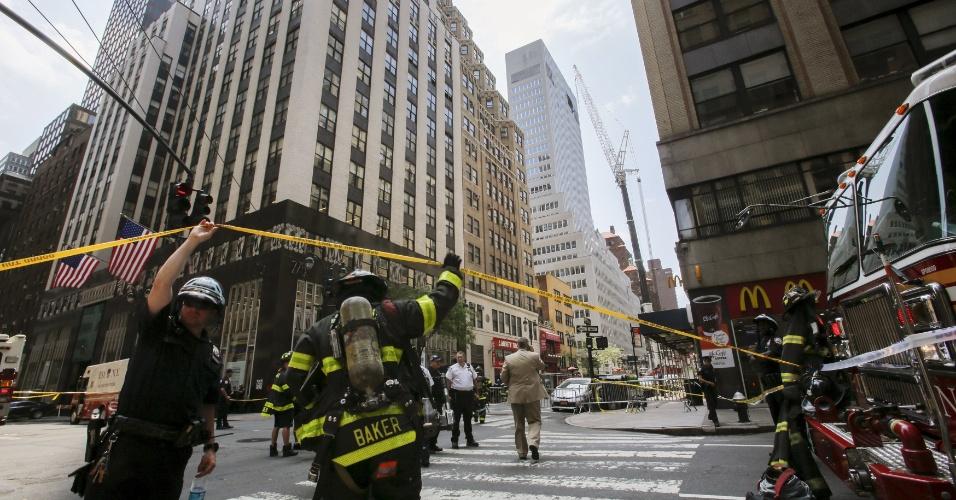 31.mai.2015 - Oficiais do Departamento de Polícia de Nova York e membros do Corpo de Bombeiros participam de um chamado de emergência após o fio de um guindaste quebrar em edifício em Manhattan. Pelo menos dez pessoas ficaram feridas