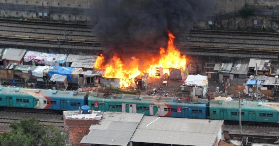 1º.jun.2015 - Barracos são atingidos por incêndio em Del Castilho, ao lado da linha férrea, na zona norte do Rio de Janeiro, na manhã desta segunda-feira (1º). A circulação do ramal de Belford Roxo, na baixada fluminense, foi interrompida próximo à estação de Del Castilho por cerca de 40 minutos por motivo de segurança, segundo a Supervia