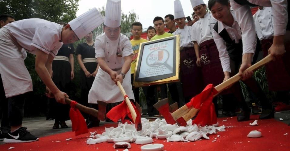 1º.jun.2015 - Cozinheiros e funcionários de restaurantes quebram cinzeiros com machados em ação antitabagismo, em Pequim, na China. A capital proibiu o fumo em restaurantes, escritórios e nos transportes públicos