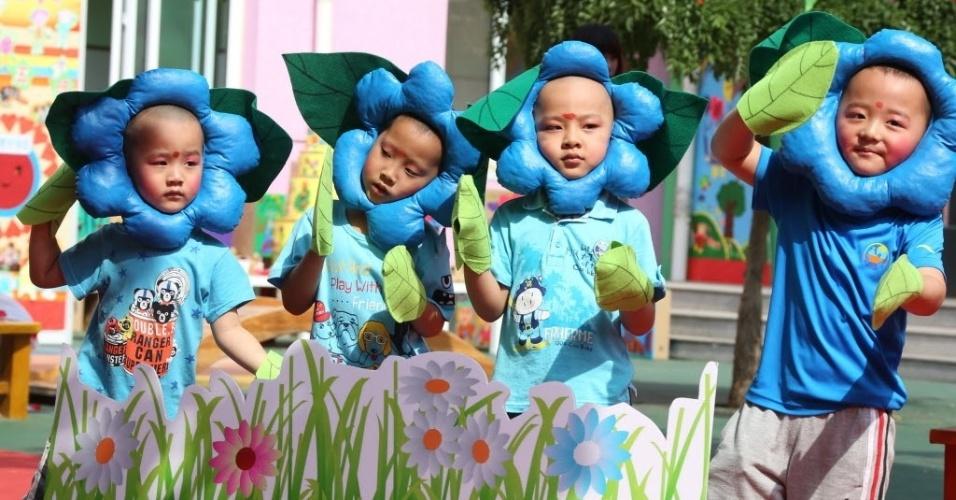 1º.jun.2015 - Crianças fantasiadas de flores dançam em um jardim de infância em Pequim, capital da China. O país comemora o Dia Internacional da Criança