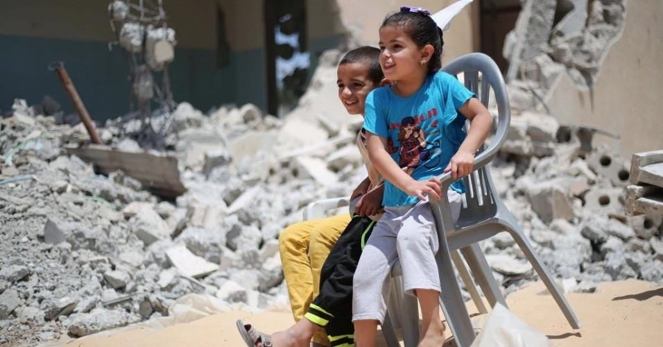 1º.jun.2015 - Crianças palestinas se sentam no meio de escombros de edifícios que foram destruídos durante o conflito que durou 50 dias entre Israel e o Hamas, em julho e agosto de 2014, na aldeia de Khuzaa, no sul da faixa de Gaza