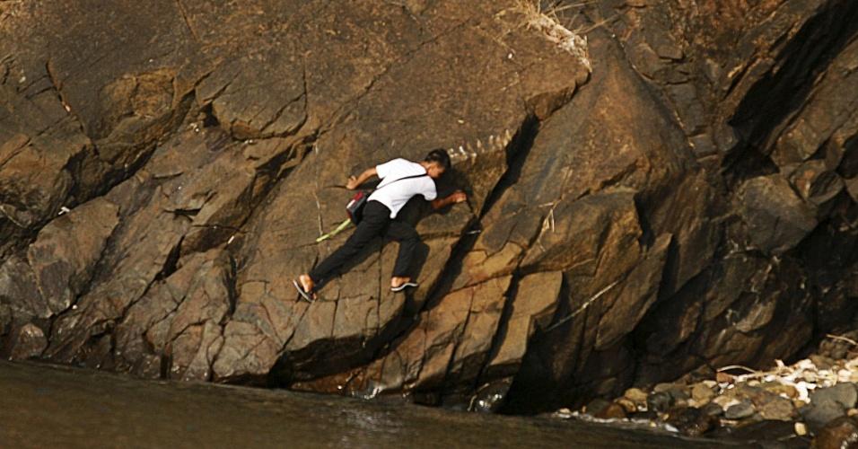 1.jun.2015 - Estudante escala rocha para ir à escola no primeiro dia letivo em Manila, Filipinas