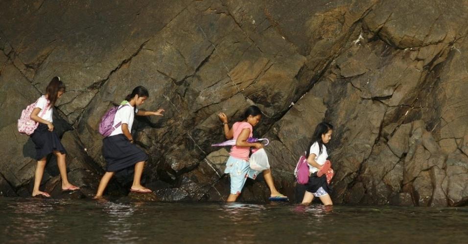 1º.jun.2015 - Estudantes filipinas tentam não se molhar durante travessia de praia rochosa em seu caminho para escola, na vila de Kawag, ao norte da capital Manila