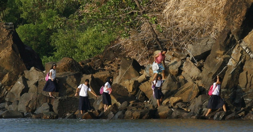 1.jun.2015 - Mulher e estudantes escalam rocha para ir à escola no primeiro dia letivo em Manila, Filipinas