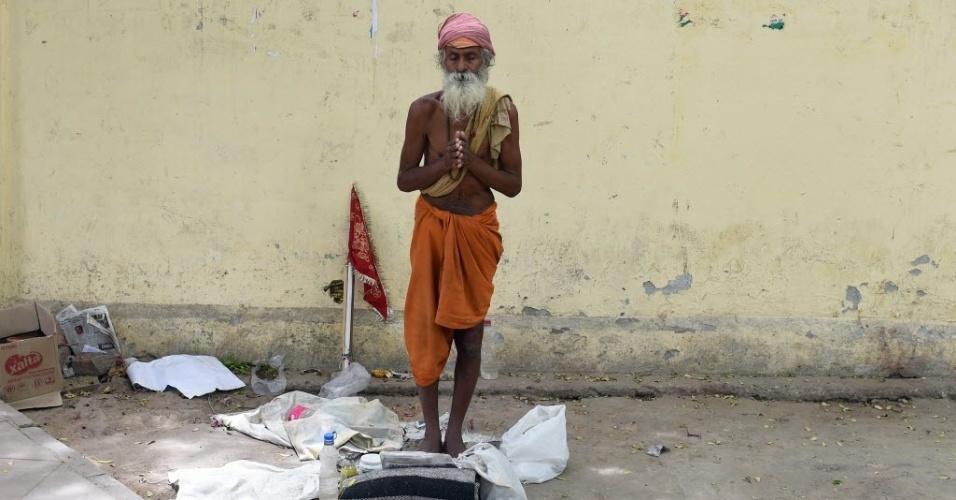 1º.jun.2015 - Sadhu, homem considerado santo, reza na beira da estrada em Nova Déli, na Índia