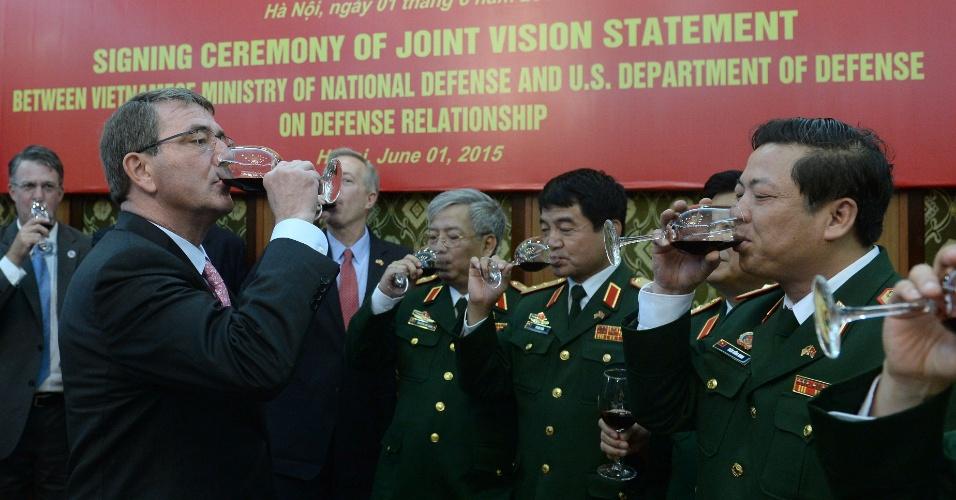 1º.jun.2015 - Secretário de Defesa dos Estados Unidos, Ashton Carter (à esq.), faz um brinde com generais vietnamitas depois de assinar um acordo bilateral com seu colega do Vietnã, o general Phung Quang Thanh, durante cerimônia no Ministério da Defesa, em Hanói