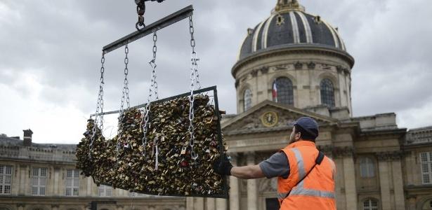 Trabalhador remove os cadeados do amor presos à Pont des Arts, em Paris