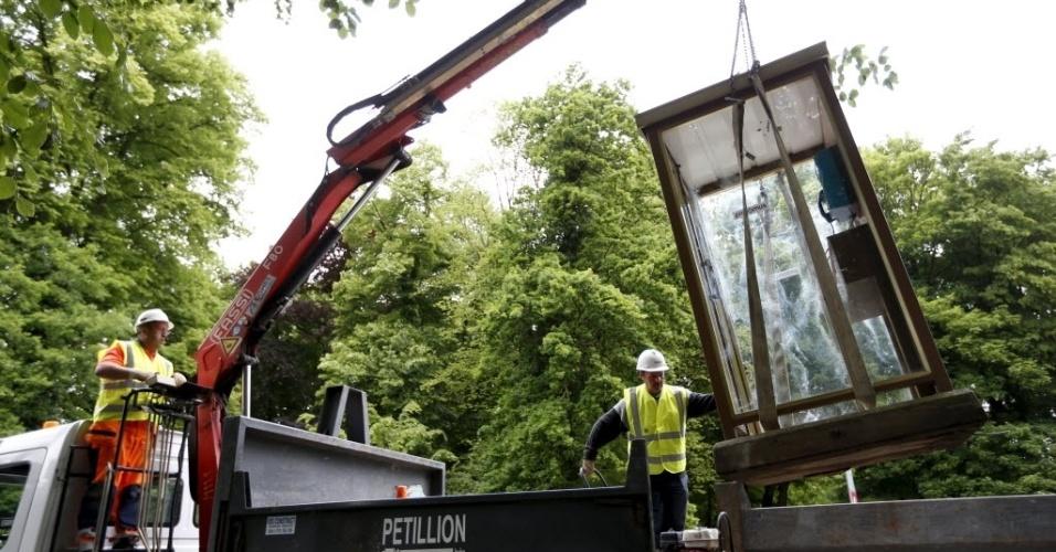 1º.jun.2015 - Trabalhadores usam um guindaste para remover a última cabine de telefone da Bélgica, durante uma cerimônia simbólica em Antuérpia