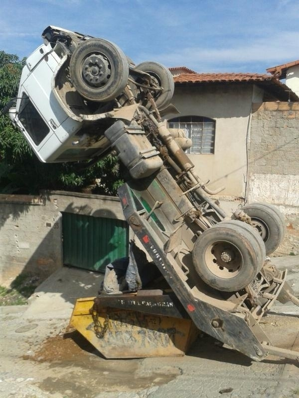 """1º.jun.2015 - Um caminhão ficou """"empinado"""" em rua da cidade de Ribeirão das Neves, cidade que fica na região metropolitana de Belo Horizonte,  nesta segunda-feira (1º). Segundo o Corpo de Bombeiros, o veículo, que transportava uma caçamba contendo areia, não conseguiu subir uma ladeira e """"empinou"""" com o peso da carga. O motorista foi resgatado sem ferimentos, e um guincho foi enviado ao local para retirar o caminhão"""
