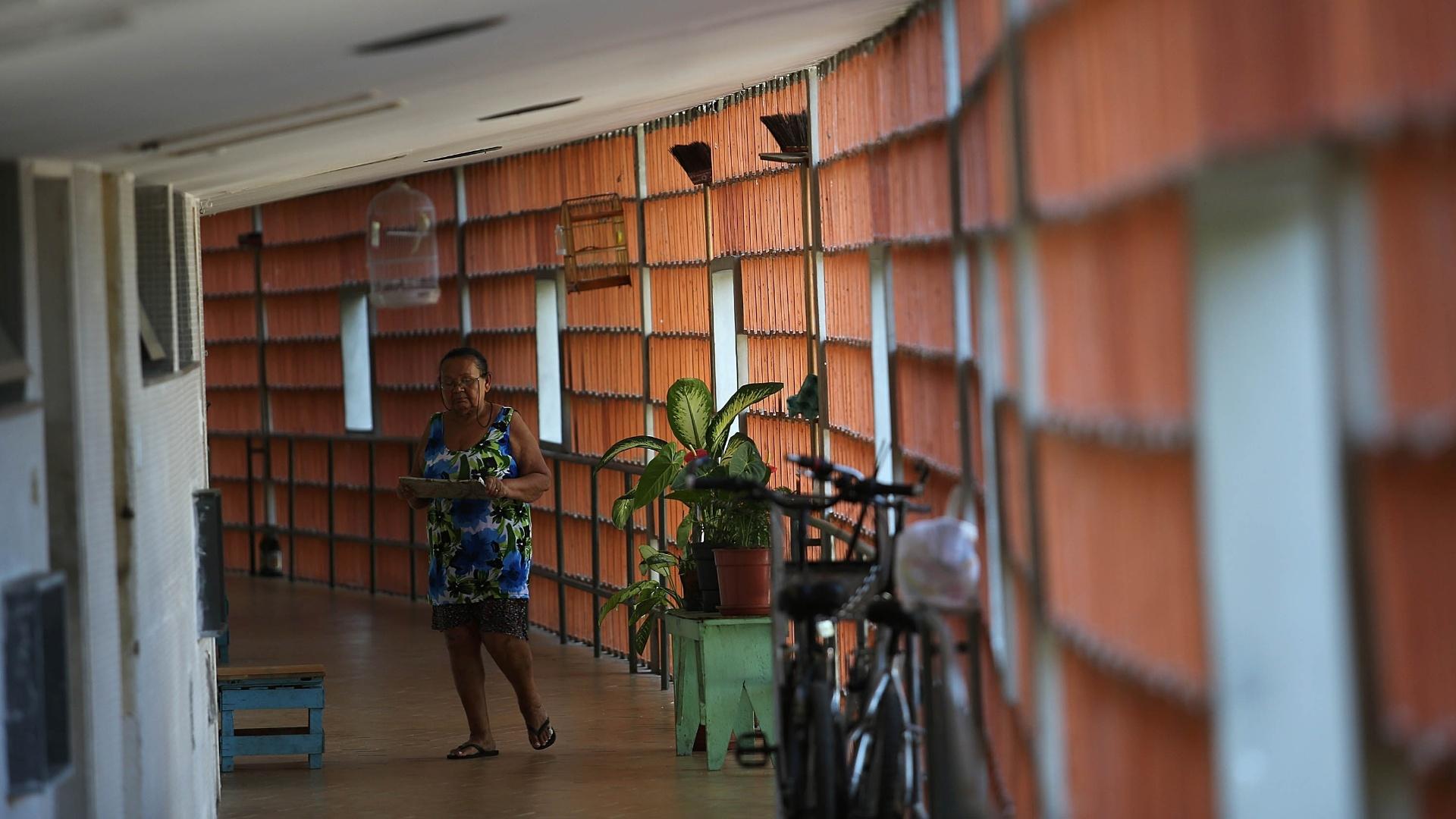 27.mai.2015 - Moradora caminha por um corredor do conjunto Pedregulho, que é considerado uma espécie de varanda dos apartamentos. No espaço podem ser encontrados animais de estimação, bicicletas, bancos, cadeiras, entre outros objetos