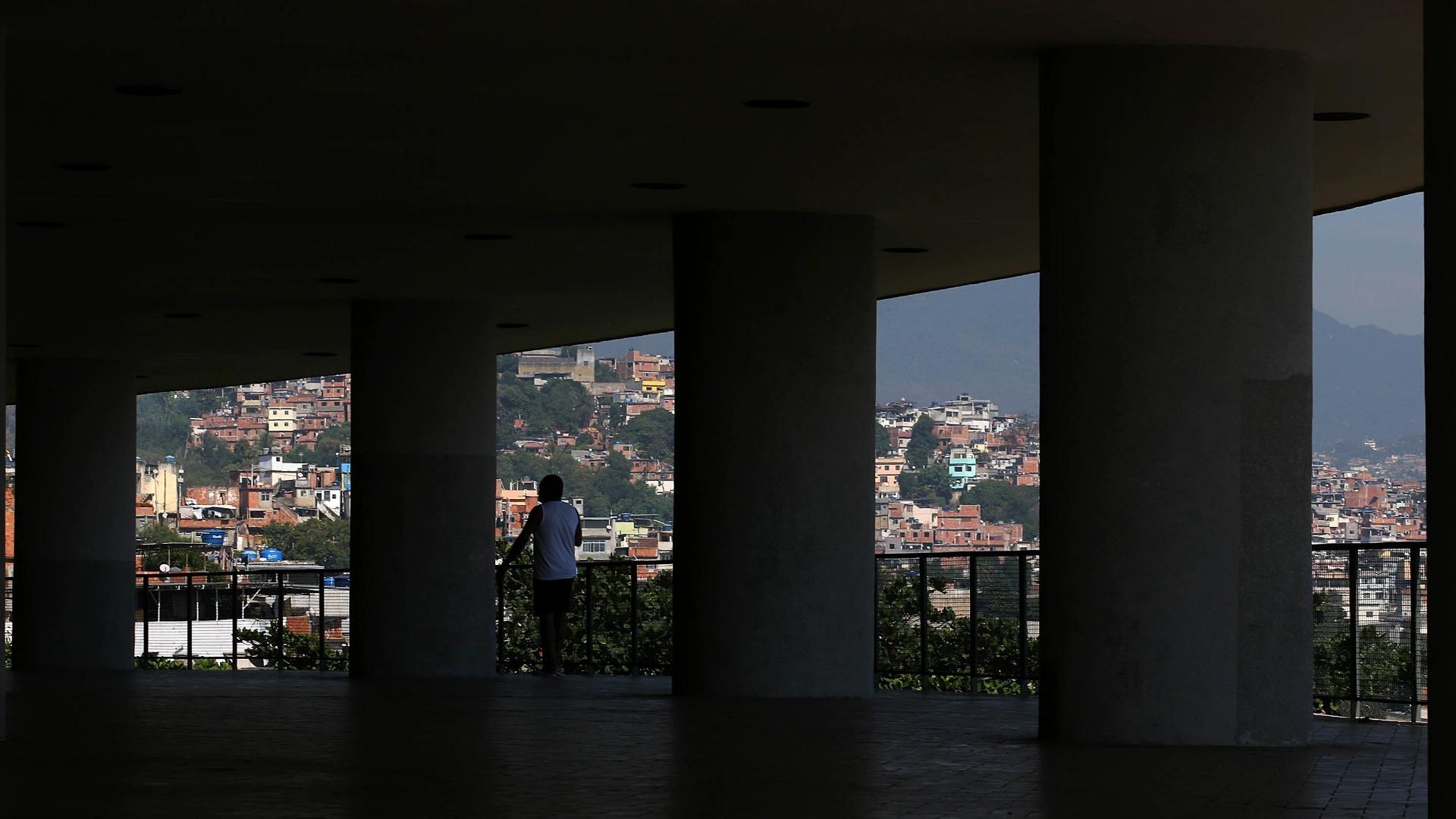 27.mai.2015 - Morador do conjunto Pedregulho caminha pelo pátio do prédio, tendo ao fundo a favela do Tuiuti, em São Cristóvão, na zona norte do Rio de Janeiro