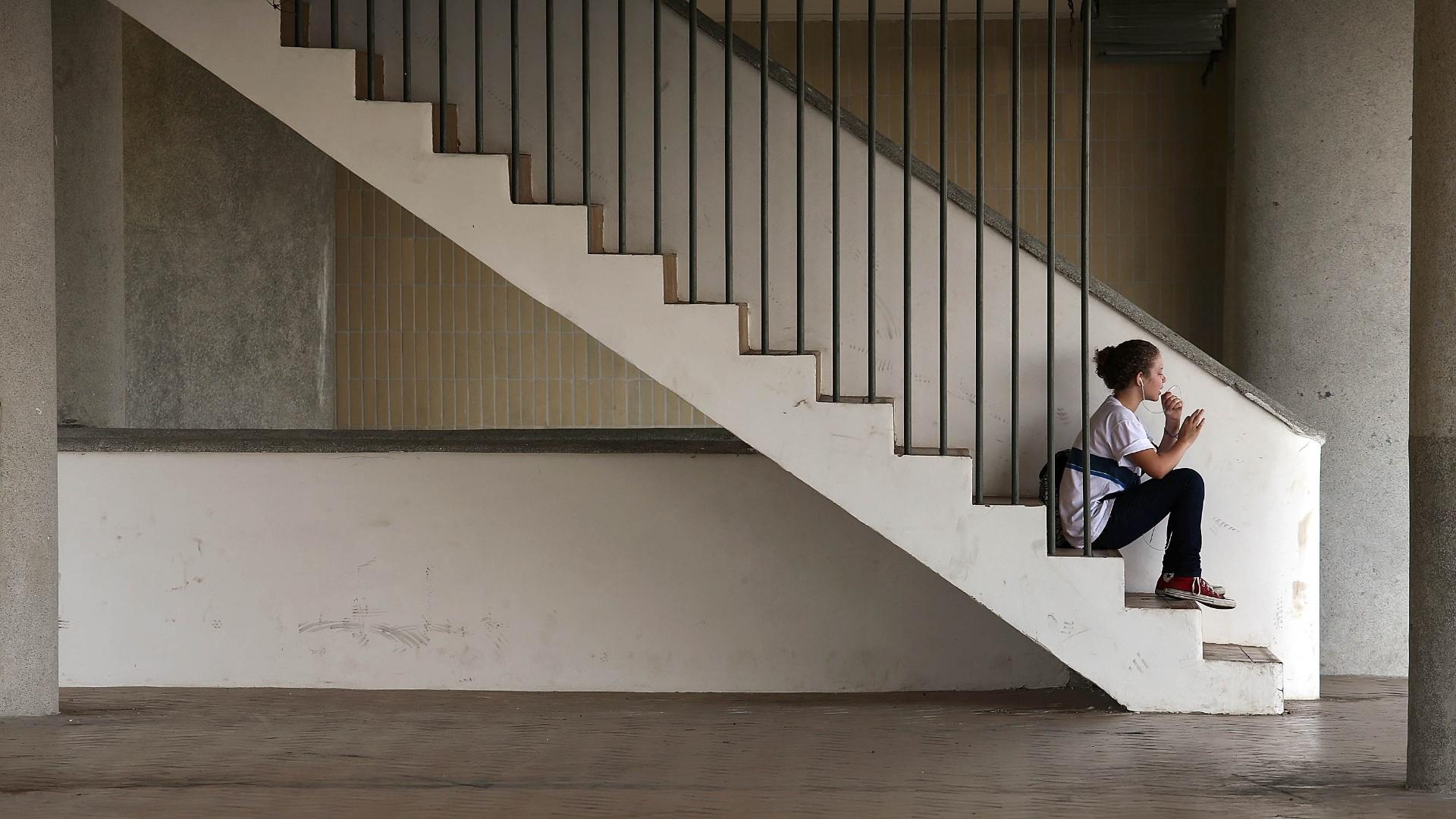 27.mai.2015 - Jovem moradora do conjunto habitacional Prefeito Mendes de Moraes, na zona norte do Rio de Janeiro, conversa ao celular sentada em escada no pavimento intermediário do prédio principal, conhecido como o pátio