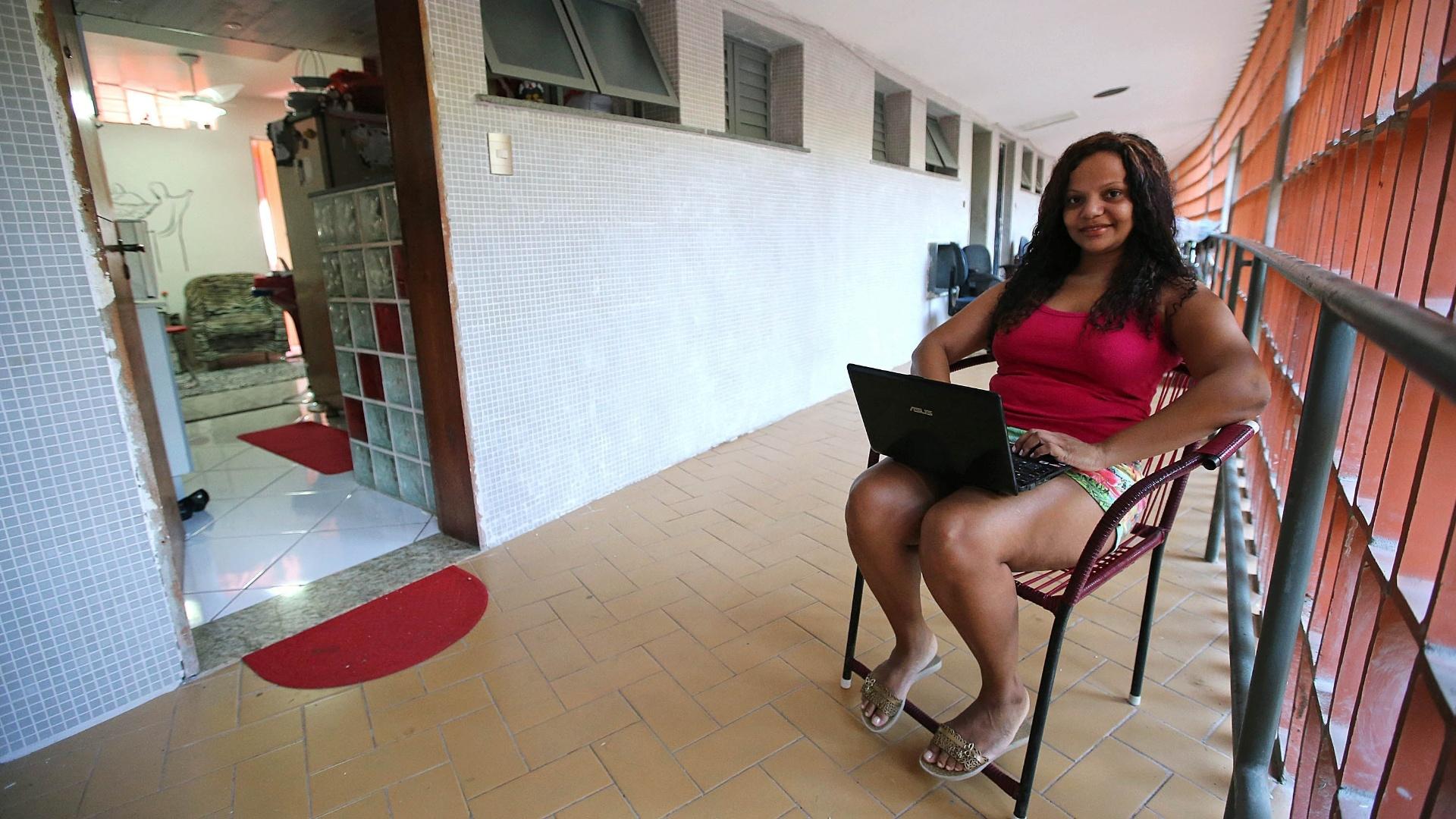 27.mai.2015 - A psicóloga Fernanda da Silva, 31, utiliza o computador no corredor na frente do apartamento onde mora sozinha, no Pedregulho.