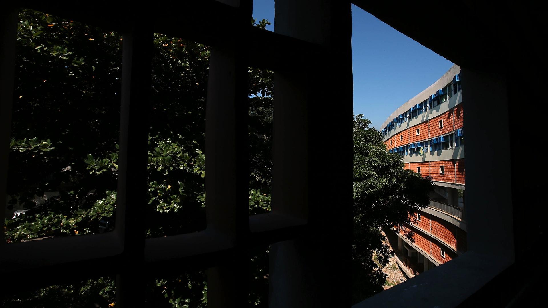27.mai.2015 - Parte da fachada restaurada do conjunto Pedregulho é vista através de uma janela. Também é possível ver a vasta vegetação que cerca o prédio